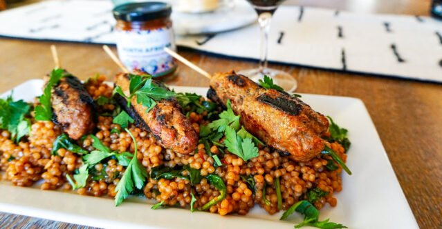 Wine-infused couscous risotto with Moroccan inspired lamb kefta kebabs on top