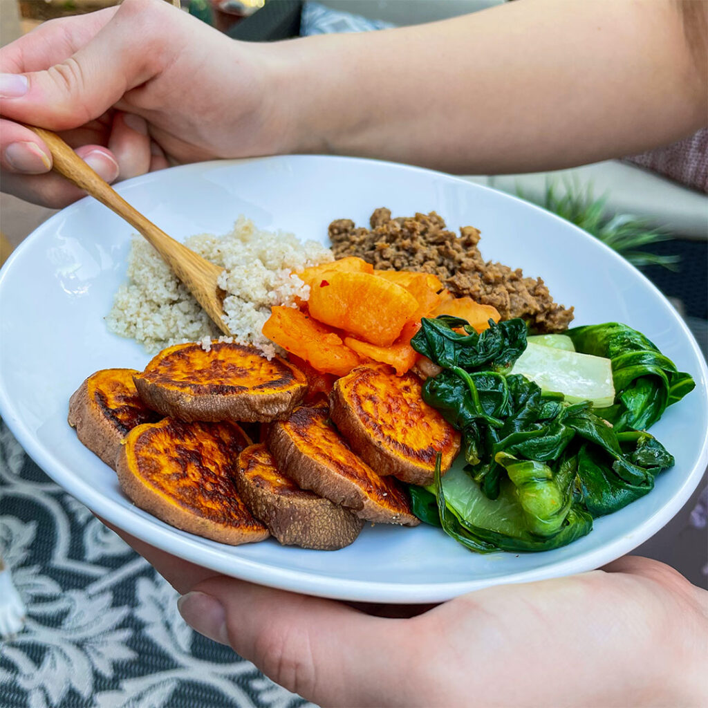 healthy protein bowl with sweet potatoes, spinach, grains, and flavorful meat or meat alternative